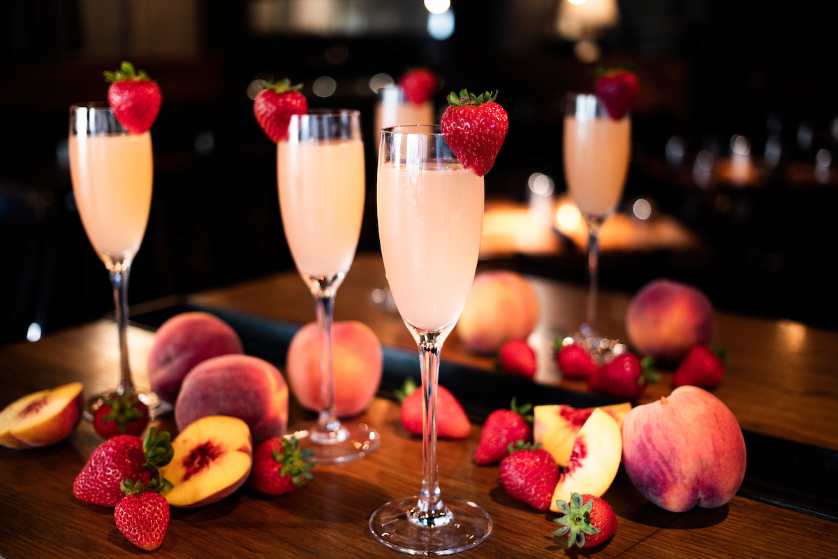 Bellinis on a table with cut up peaches
