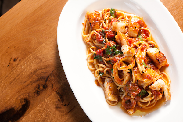 The seafood pasta from Osteria Via Stato on a wooden table