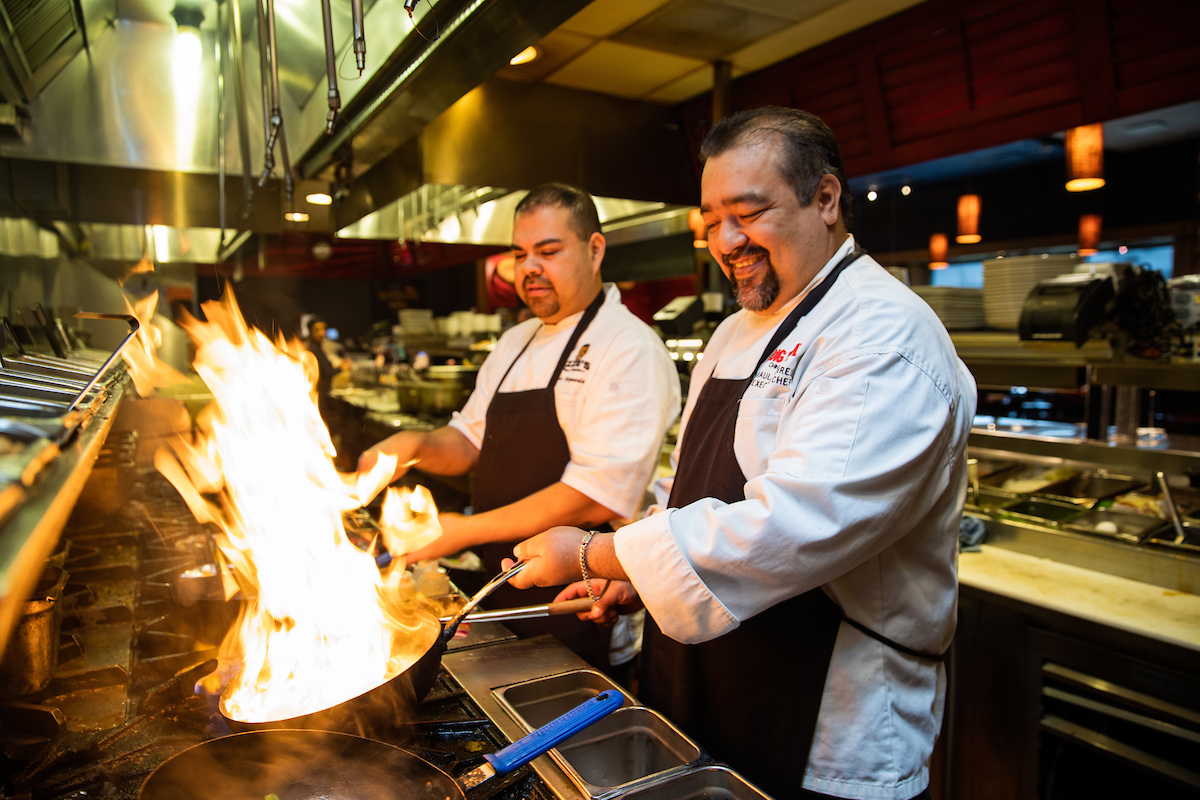 Raul and Ozzie working a wok