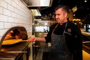 Chef Joe tends to the pizza oven at Antico Posto