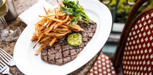 Steak frites plate on table with bistro chair
