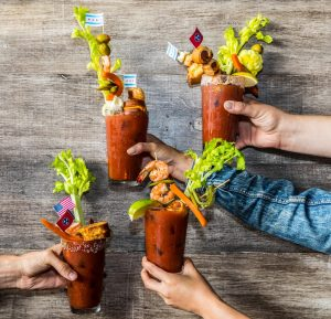 Four bloody marys in front of a wall