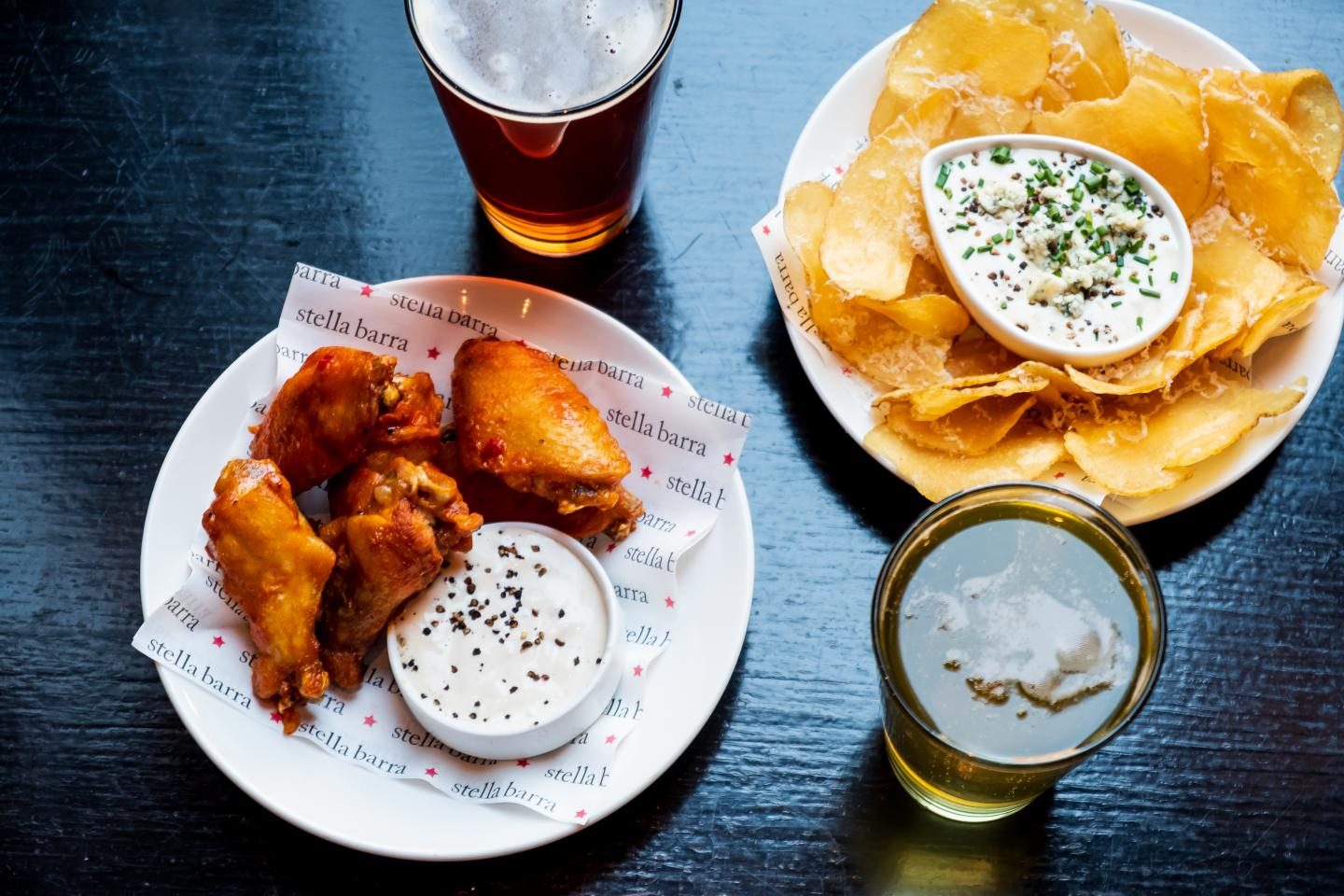 Wings, Chips and Beers on a table at Stella Barra