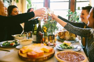 People cheers-ing around a Thanksgiving table at home