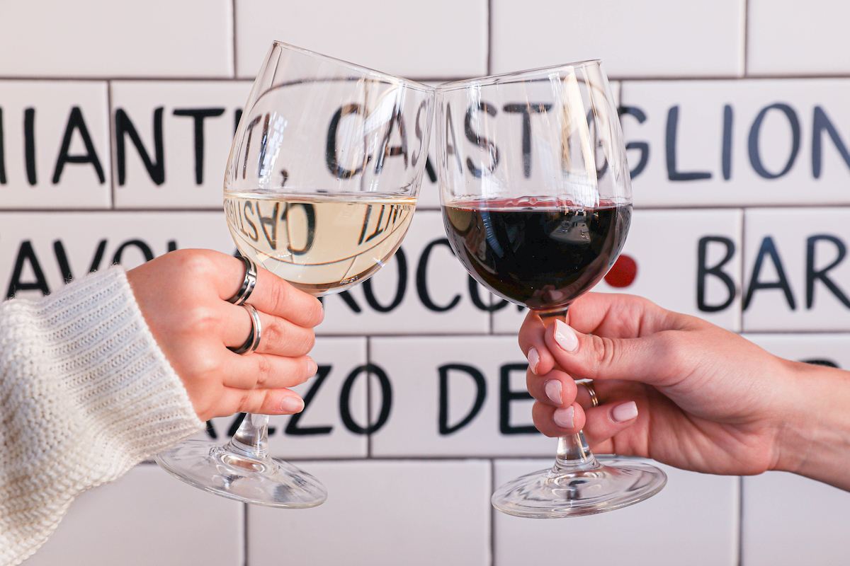 Two people holding a glass of white and red wine