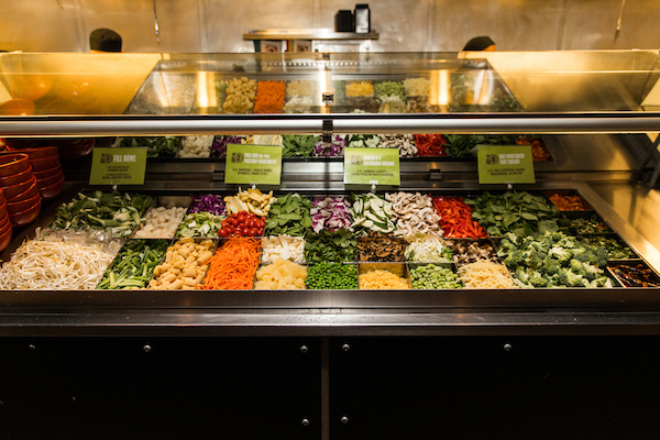 A stir fry bar filled with vegetables