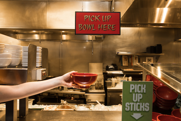 "A hand holding out a bowl below a sign that says ""Pick Up Bowl"" in a Big Bowl"