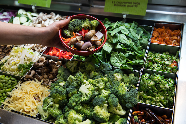 A hand holding out a bowl of vegetables over the stir fry bar at Big Bowl