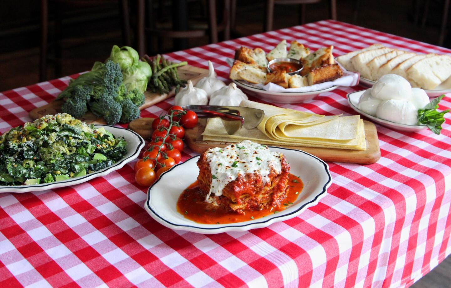 burrata lasagna, green chopped salad and tuscan cheese bread on table with ingredients