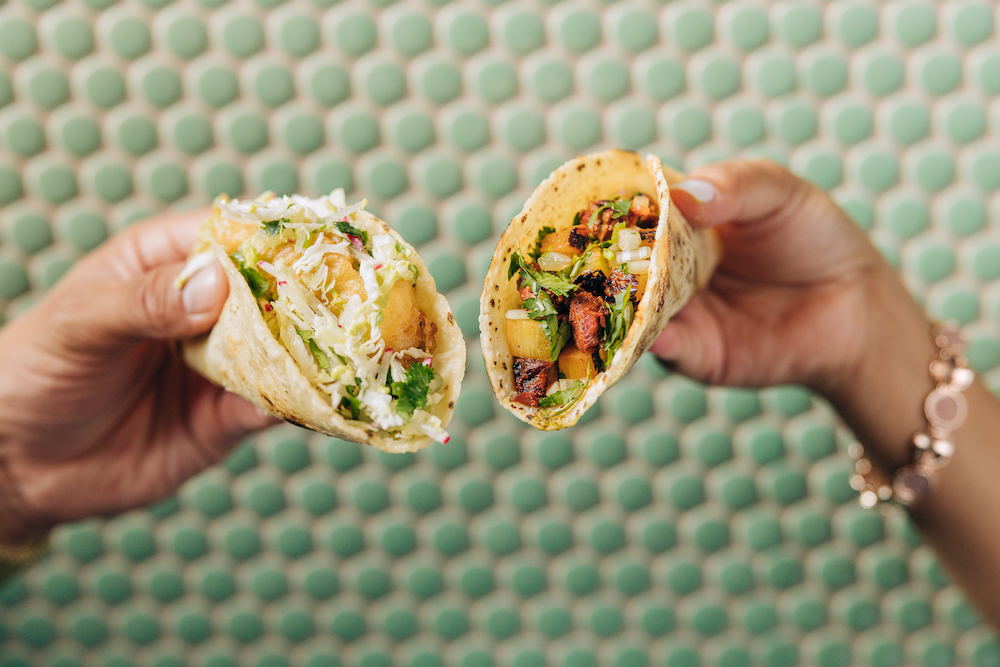 two hands holding two tacos against green background