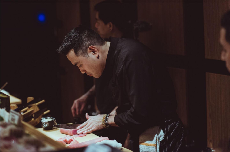 sushi chef kaze chan cutting fish at the sushi counter