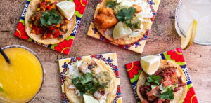Authentic Mexican two-bite tacos and margaritas on decorative tiles