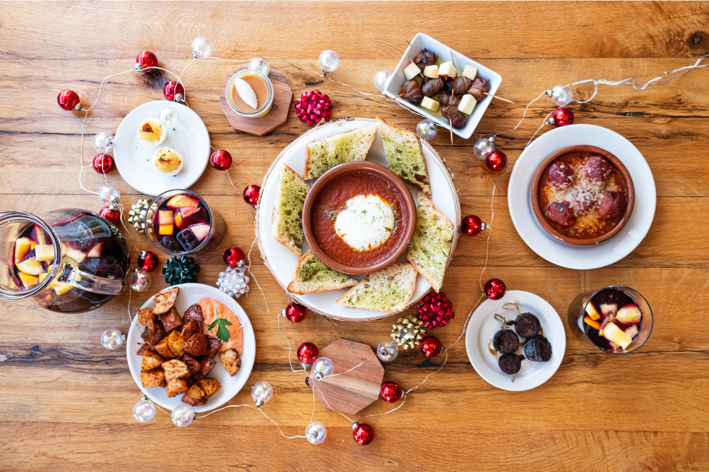 Spanish tapas with goat cheese, deviled eggs, spicy potatoes and holiday ornaments strung along a dining table.