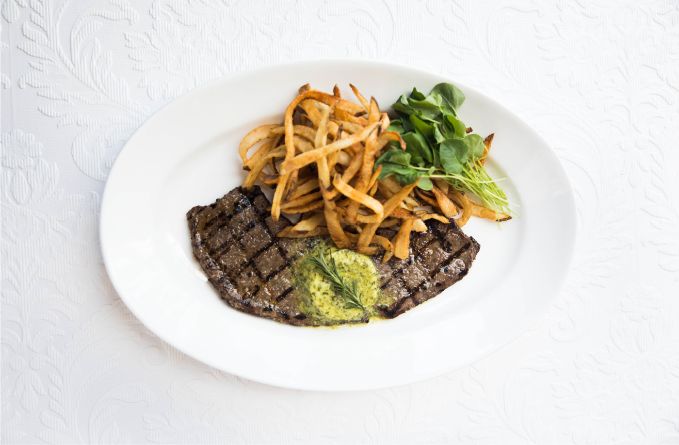 Plate of Steak Frites with maitre d'hotel butter and garnish on white French background.