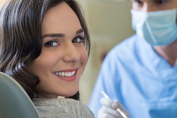 Smiling young woman receiving dental checkup every 6 months