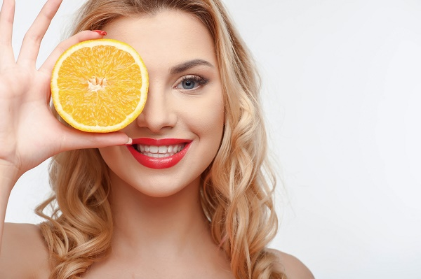 Cheerful girl is covering her eye with orange. She is smiling with enjoyment. Isolated on background and there is copy space in right side