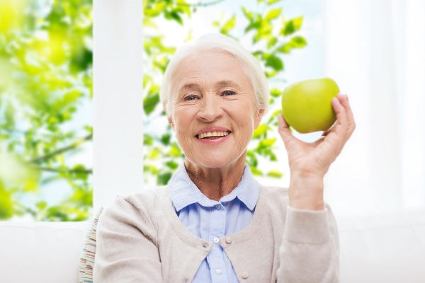 age, healthy eating and people concept - happy smiling senior woman with green apple at home over window and green natural background
