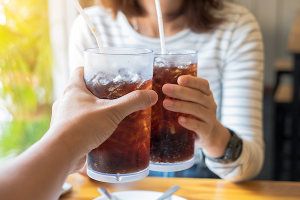 Men and Woman hand giving glass of cola.Glass of cola ,Soft drinks with ice, sweethart or buddy