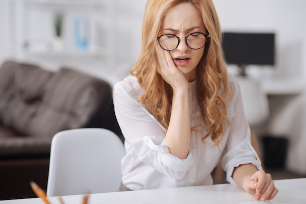Need to see dentist. Puzzled upset young worker sitting at the workplace while touching her cheek and suffering from aching teeth