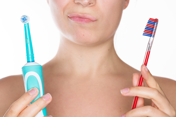 Young beautiful woman undecided whether to use the electric or traditional toothbrush, isolated over a white background
