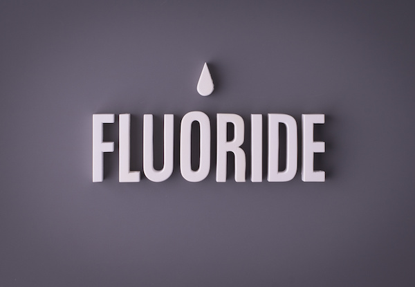 Fluoride lettering sign made with colorful background and white ceramic letters.