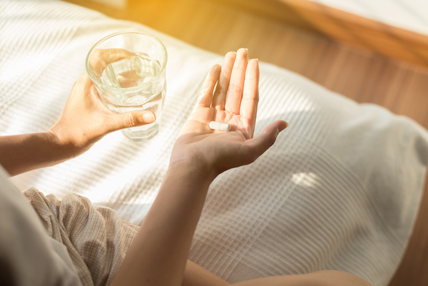 Woman with pills or capsules on hand and a glass of water