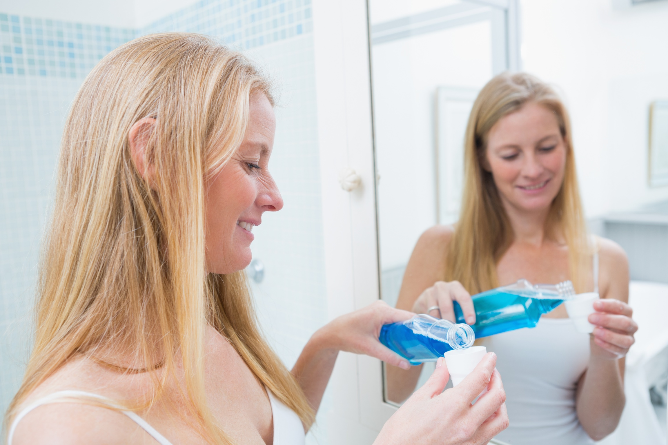 Woman practicing good oral hygiene by using mouthwash.