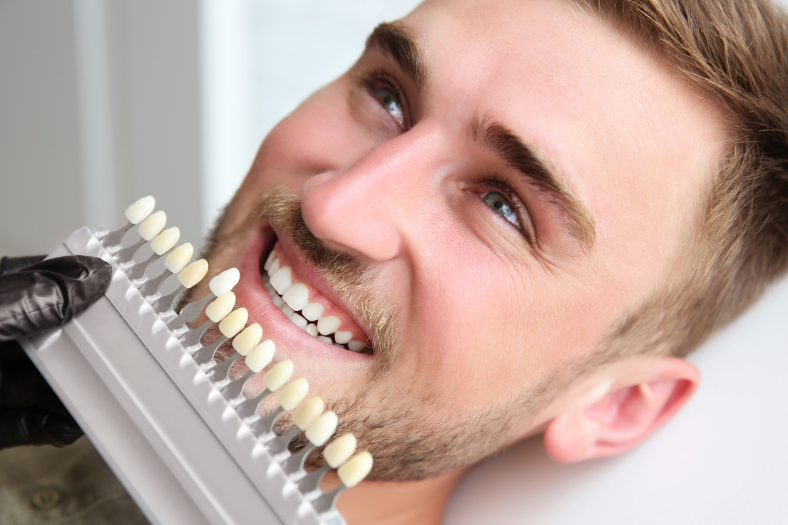 Young man choosing color of teeth at dentist.