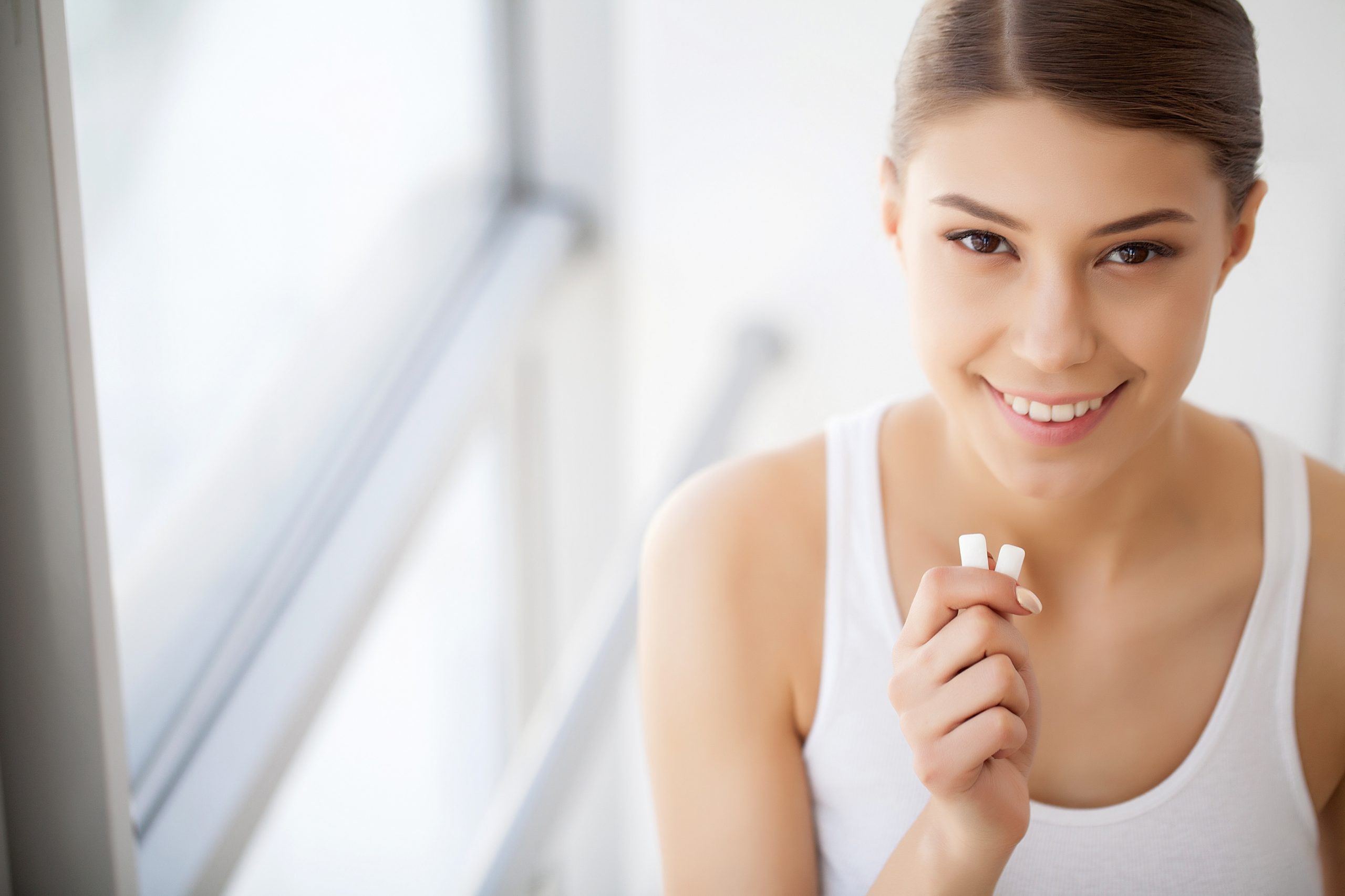 Beautiful young woman eating chewing gum, smiling