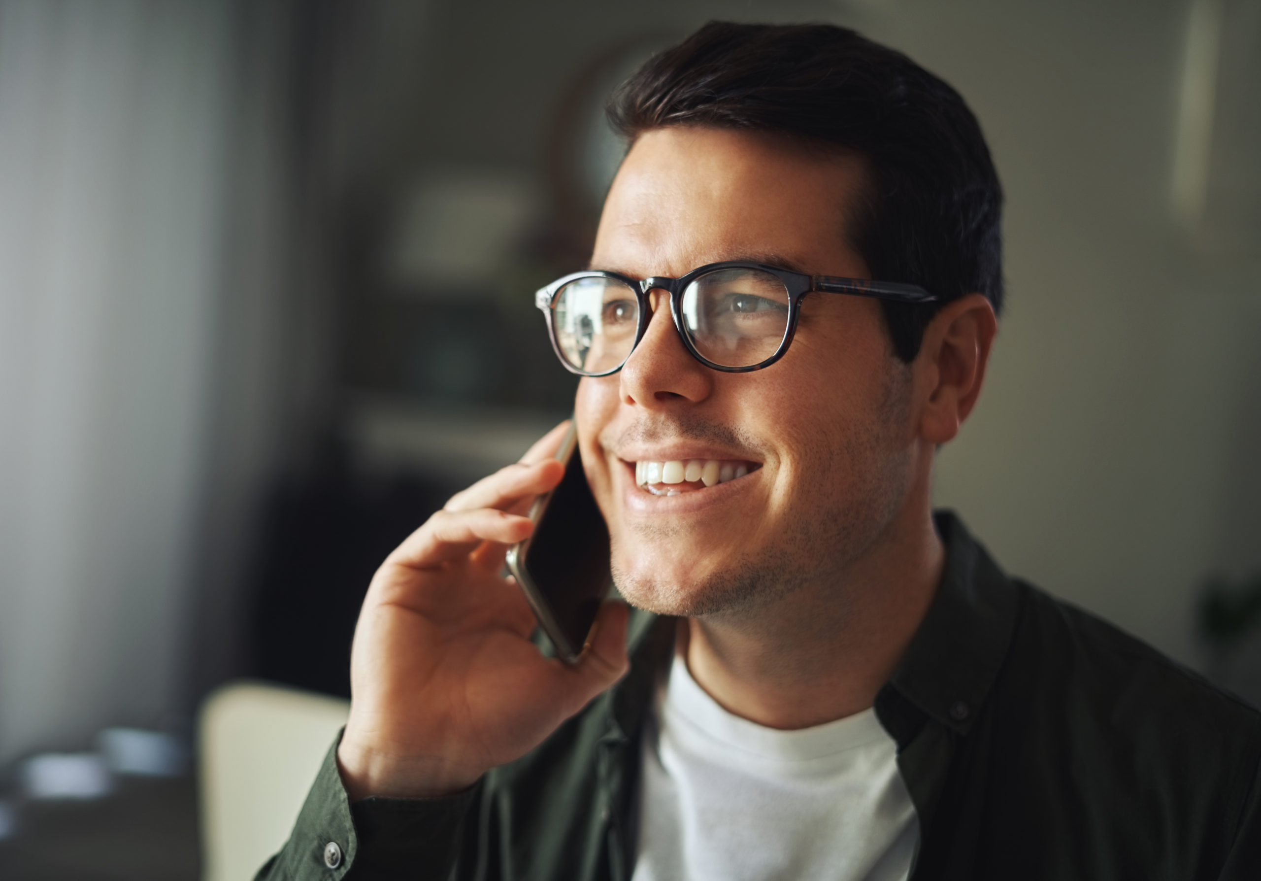 Smiling handsome man wearing black eyeglasses talking on a mobile phone