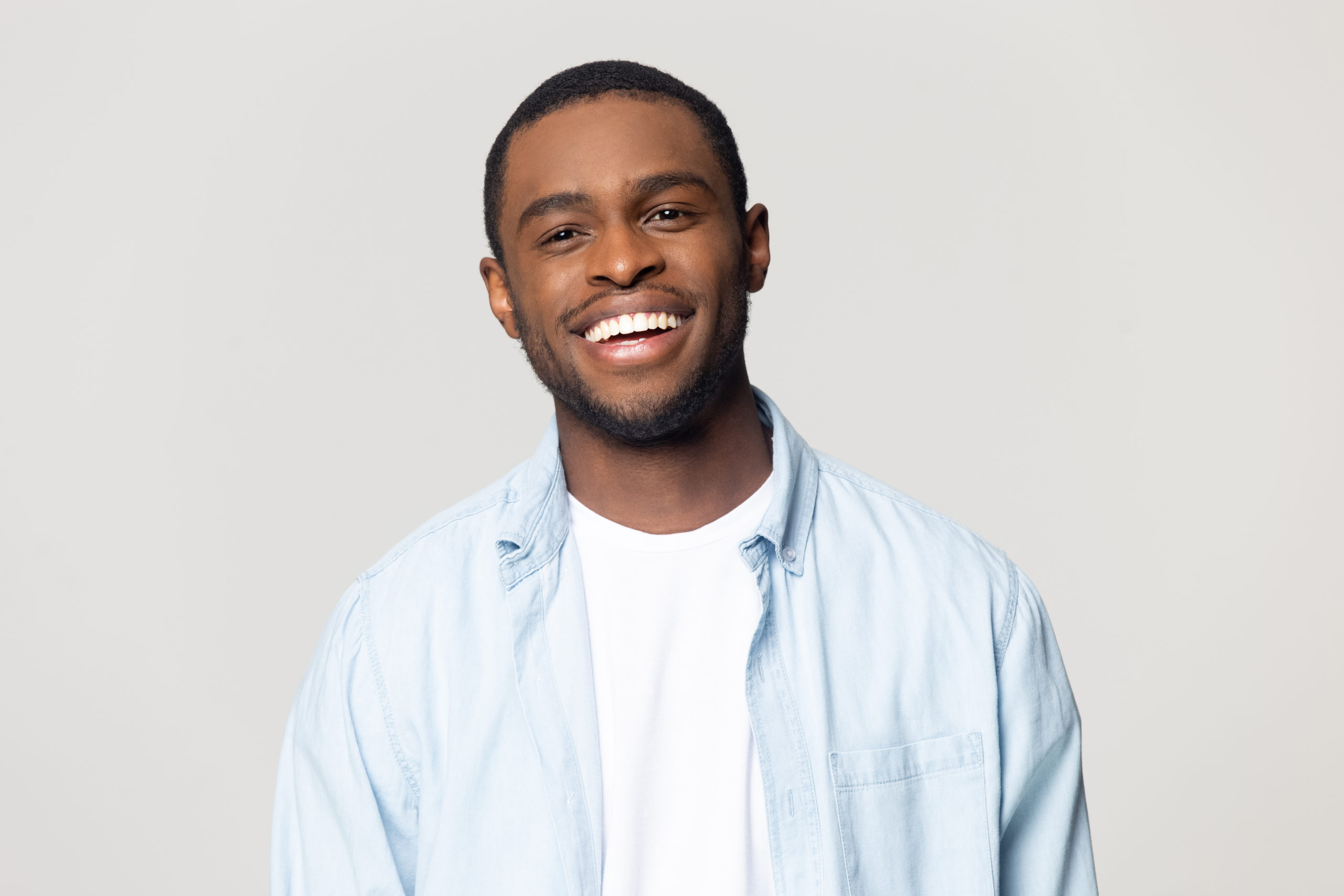 Head shot portrait happy African American man with wide healthy smile, satisfied client customer looking at camera, handsome young male feeling positive, isolated on grey background