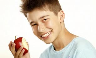 teenage boy eating an apple