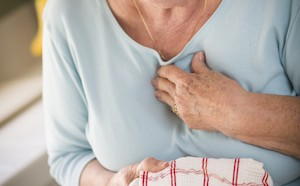 Senior Adult Woman At Kitchen Sink With Chest Pains