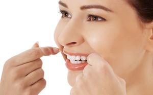 Beautiful woman with dental floss