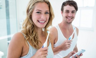 Young couple preventing oral disease by brushing their teeth at home