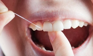 man flossing to prevent periodontal disease