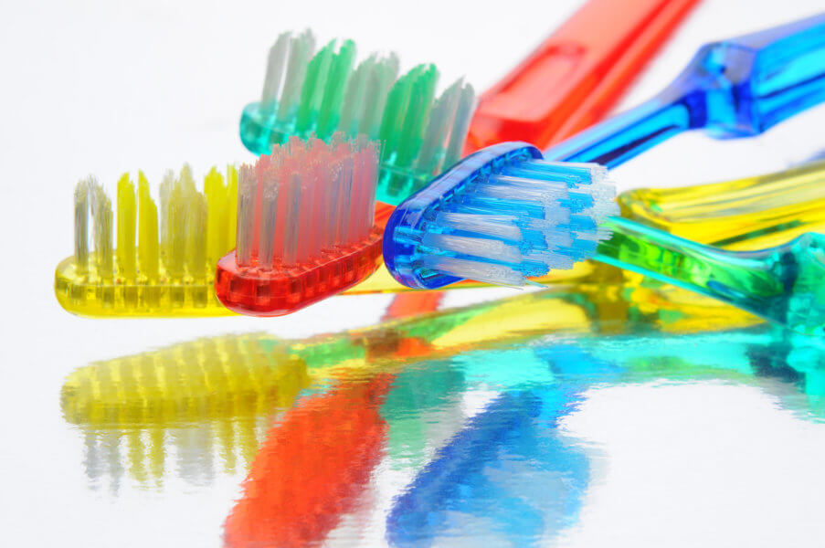 Closeup of several toothbrushes laying on a reflective surface. Horizontal format.