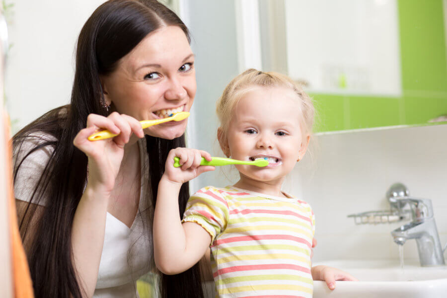 happy family mother and daughter kid girl brushing teeth together