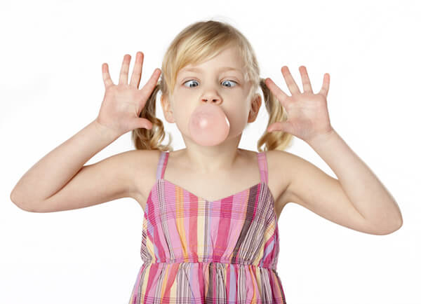 Studio photo of small female child blowing a bubble with gum. White background.