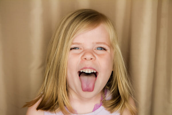 Young girl sticking her tongue out making a funny face