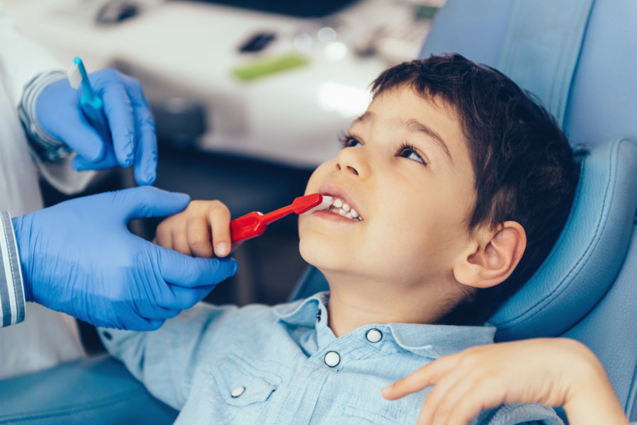 Dentist with little boy, talking about dental hygiene