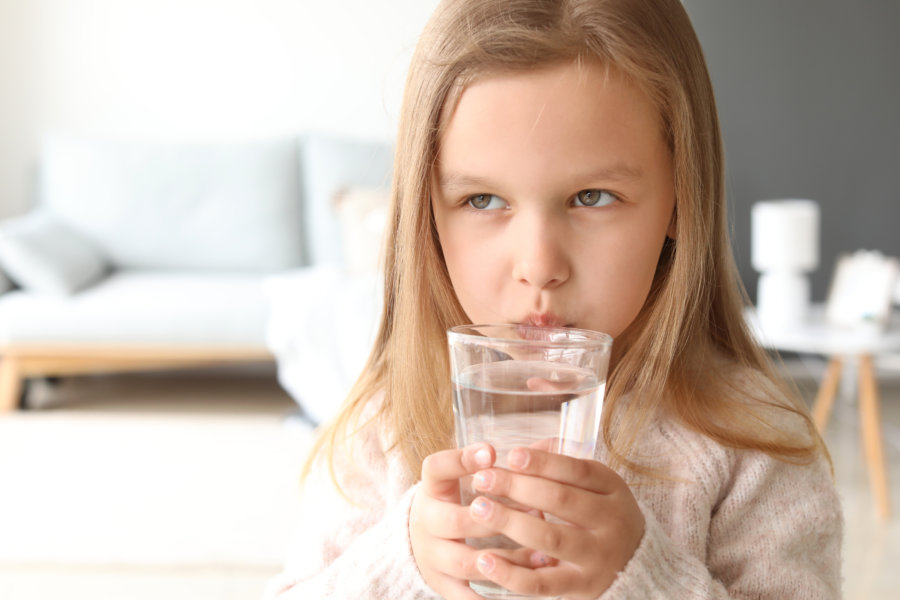Cute little girl drinking water at home