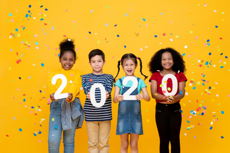 Cute smiling mixed race kids showing numbers 2020 celebrating new year isolated on yellow background