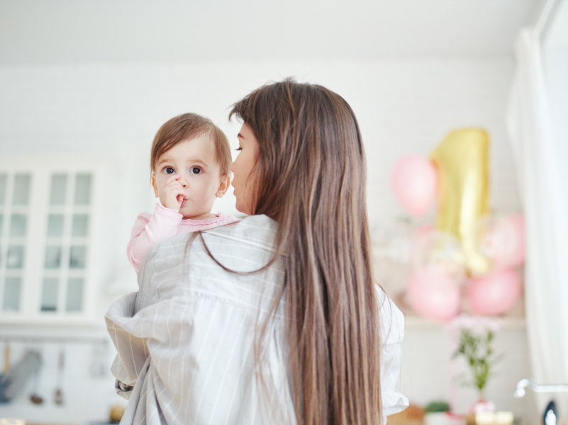 Rear view of young mother with long hair holding baby daughter sucking thumb and talking to her on first birthday