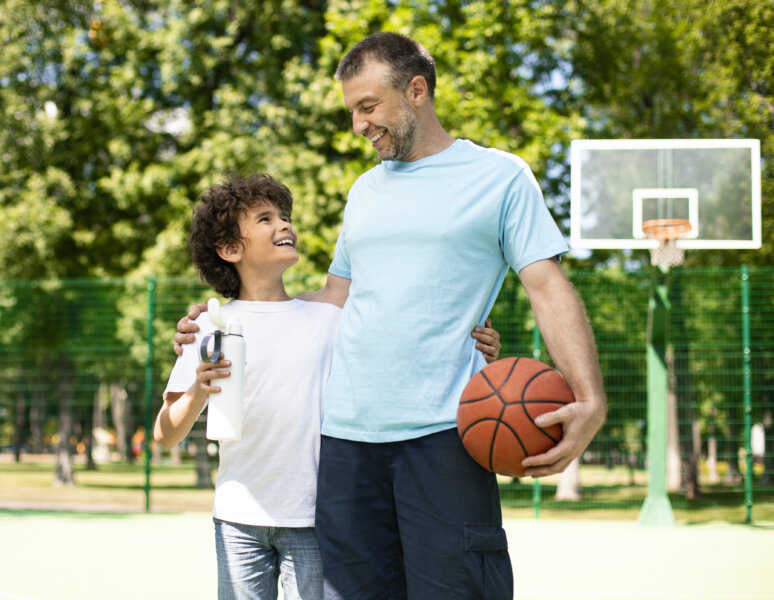 electrolytes and hydration Weekend Concept. Father and son hugging on playground, holding basket ball and water thermos bottle