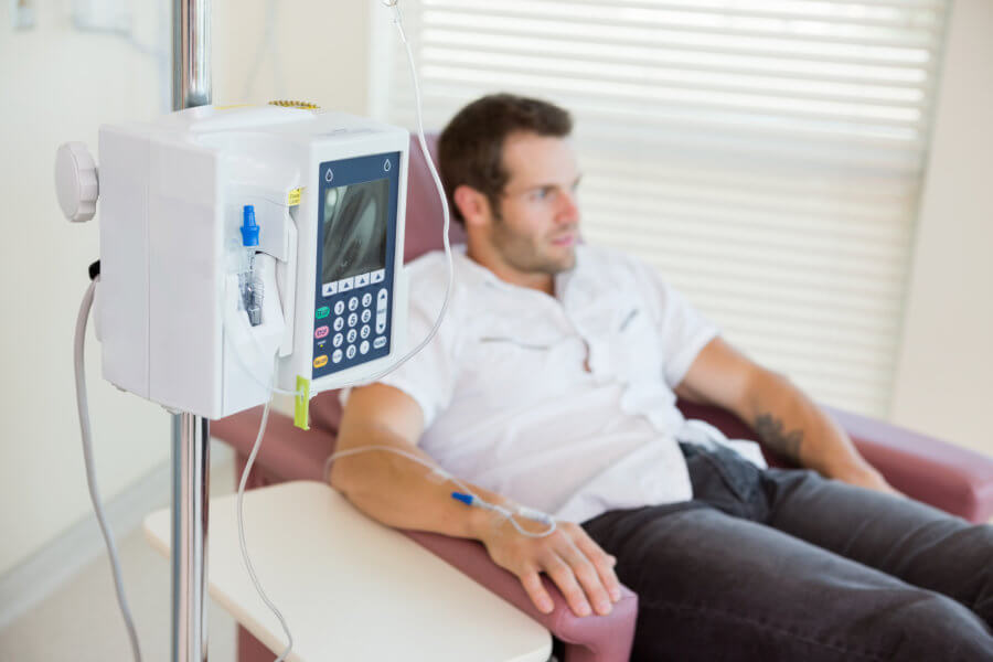 IV drip attached to young male patient's hand during chemotherapy in hospital room