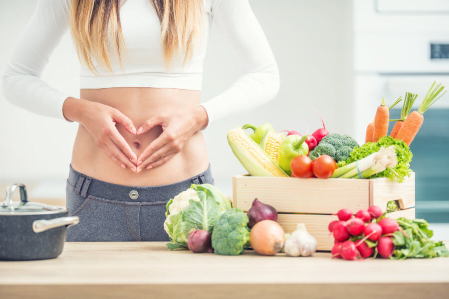 Woman with sports figure on her belly shows heart shape in home kitchen with wooden box full of organic vegetable.