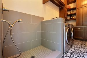 Laundry Room with Half-Height Pet Shower, Custom Storage, Hanging Rod and Side-By-Side Washer and Dryer