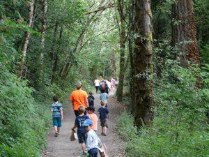 A group of children - led by a chaperone - explore the wonders of Crown Park trails