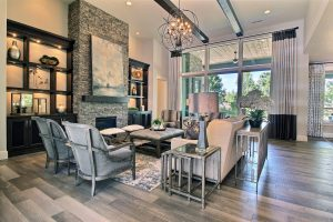 Great Room with Built-In Cabinetry, Stained Overhead Beams and Stone Fireplace Surround
